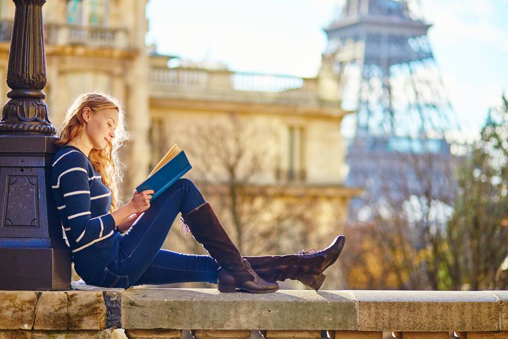 Femme lisant assis sur un mur avec la Tour Eiffel en arrière-plan