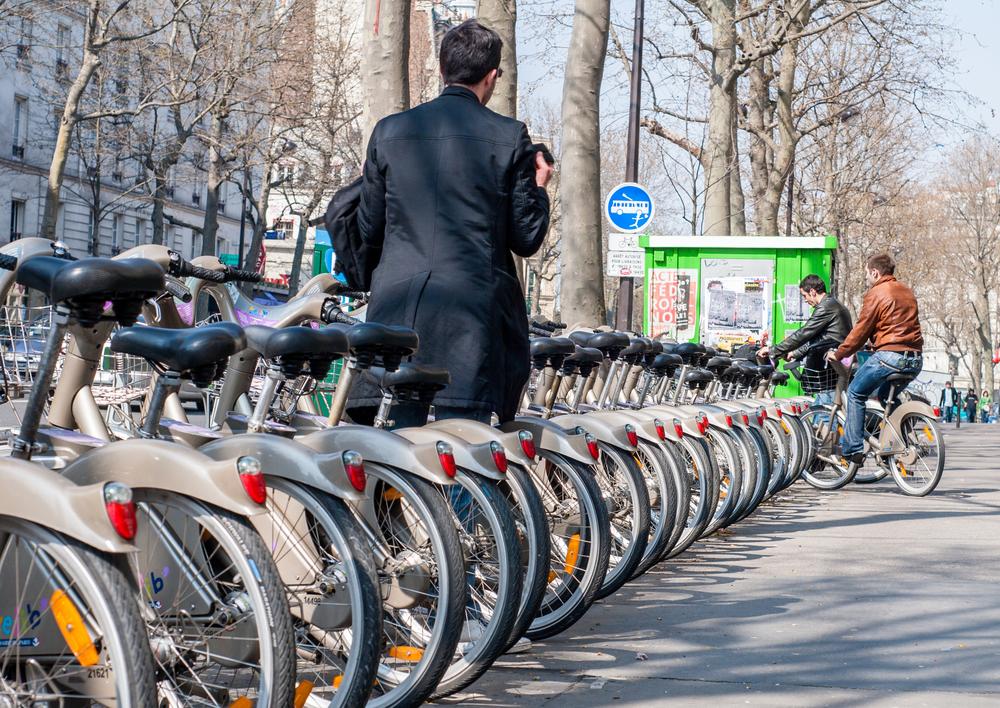 Ligne de vélos à Paris avec homme choisissant lequel rouler