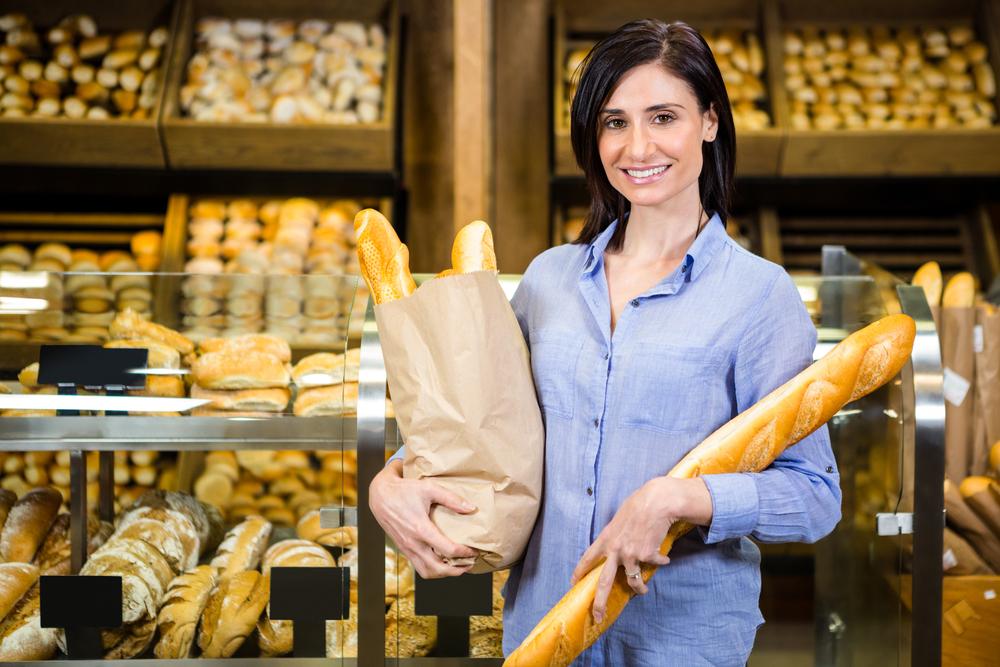Femme achetant une baguette dans une boulangerie française