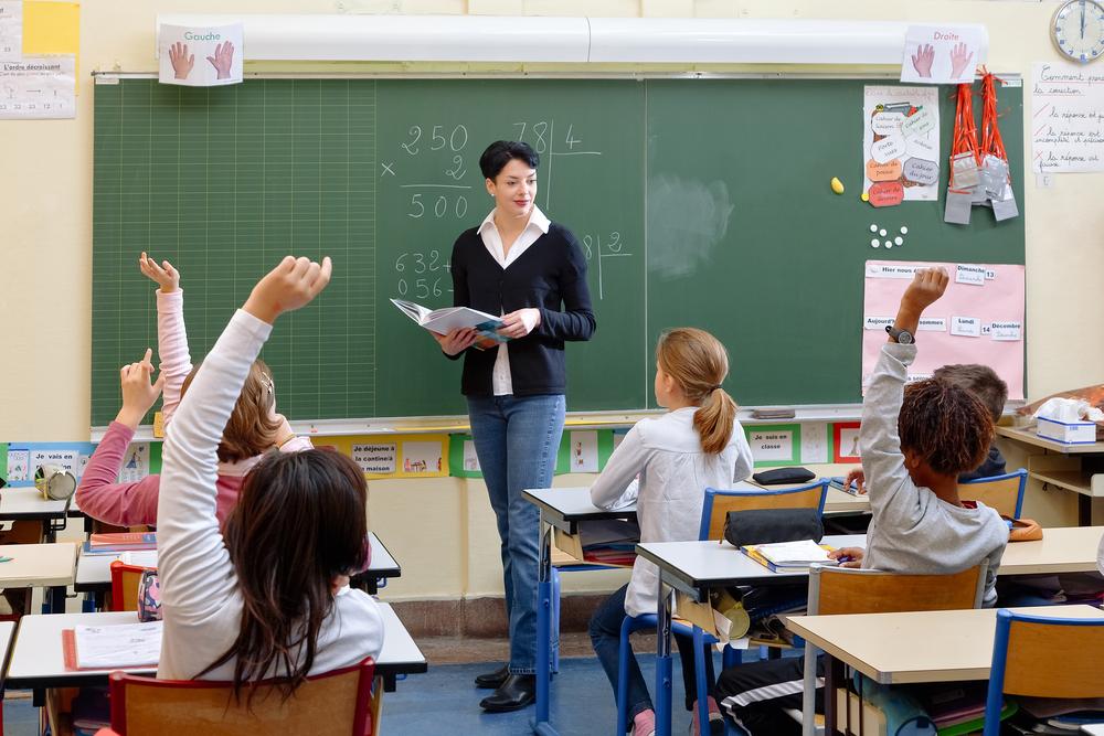 Les enfants de l'école dans une classe de français avec un enseignant debout devant eux