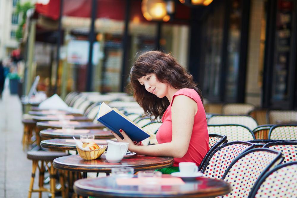Femme assise au café français lire et apprendre le français