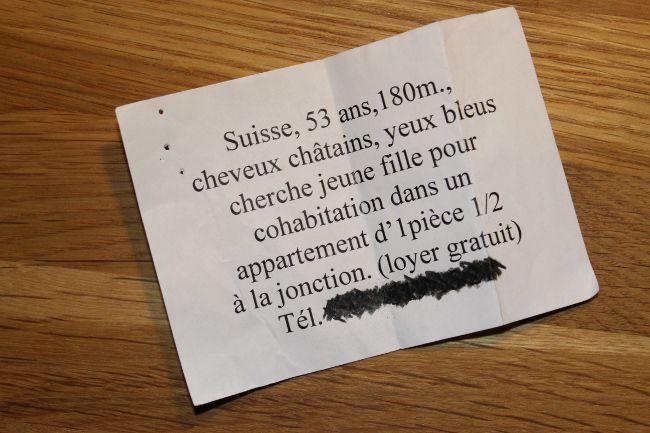 Paper with text: Suisse, 53 ans, 180m, cheveux châtains, yeux bleus cherche jeune fille pour cohabitation dans un appartement d' 1 piece ½ a la joncyion (loyer gratuit).