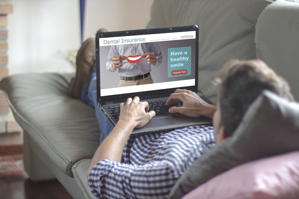 Man typing on laptop searching for dental insurance plan
