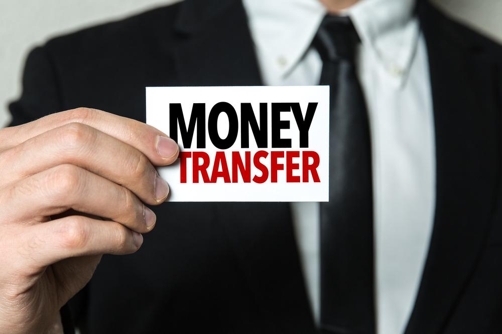 Man's hand holding sign 'Money Transfer'