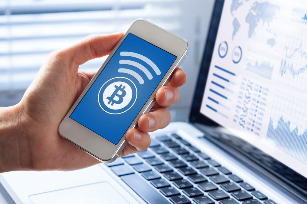 Bitcoin - man holding phone near computer making a Bitcoin transaction