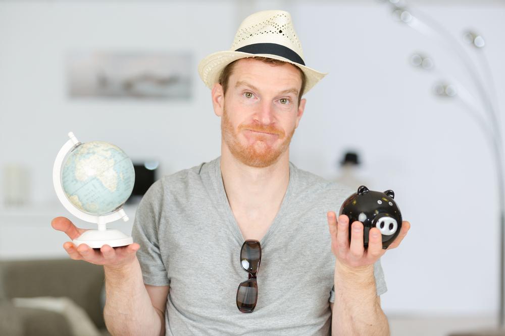 Millenial man golding a globe and piggy bank