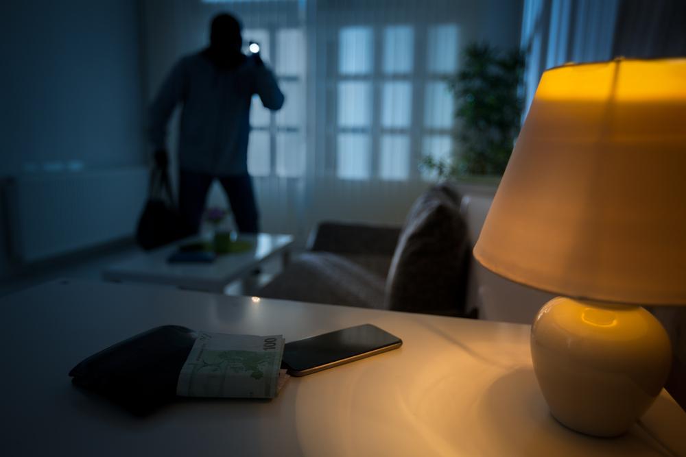A burglar entering a home at night